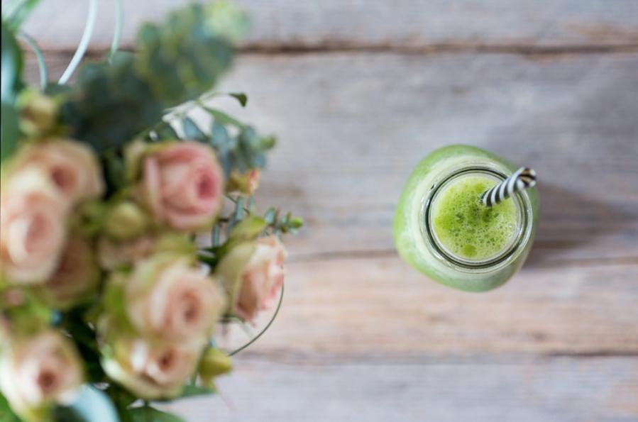 rosas en mesa con smoothie verde